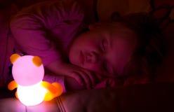 Mädchen, das mit hellem Spielzeug schläft Stockbild