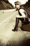 Mädchen, das mit Koffer trampt Lizenzfreie Stockbilder