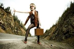 Mädchen, das mit Koffer trampt Stockfotografie