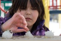 Mädchen, das mit Schnee spielt Stockfotos