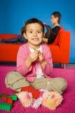 Mädchen, das mit Spielzeugblöcken (Mutter, spielt hinter ihr) Stockbild