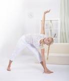 Mädchen, das Muskeln ausdehnt Stockfoto