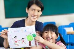 Mädchen, das Mutter eine Zeichnung gibt Stockbilder
