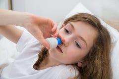 Mädchen, das nasalen Spray verwendet Lizenzfreie Stockfotografie