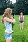 Mädchen, das Pfeil des Verbundbogens auf Apfel auf Kopf der Frau abzielt Stockbild