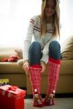 Mädchen, das rote Weihnachtssocken trägt Stockbilder