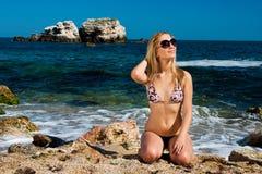 Mädchen, das am Seestrand ein Sonnenbad nimmt Lizenzfreies Stockfoto