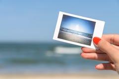 Mädchen, das sofortiges Foto des Seestrandes hält Lizenzfreie Stockfotografie