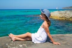 Mädchen, das Strand in Formentera-Türkis Mittelmeer betrachtet Stockfotos