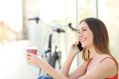 Mädchen, das um den Handy ersucht und Kaffee trinkt Lizenzfreie Stockfotografie