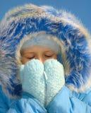 Mädchen, das versucht, ihr Gesicht zu wärmen Lizenzfreies Stockbild
