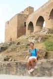 Mädchen, das vor einzigartiger Brücke auf Velhartice-Schloss sitzt Stockbilder