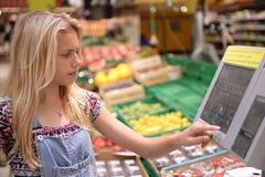 Mädchen, das Waren im Shop wiegt Stockfoto