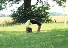 Mädchen, das Yoga auf Wiese ausübt Stockbilder