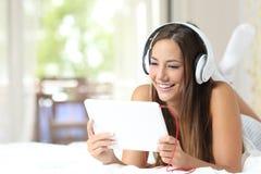 Mädchen, das zu Hause Musik von einer Tablette hört Stockfoto