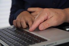 Mädchen, das zu ihrem Großvater mit dem Computer hilft Stockfoto