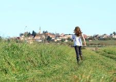 Mädchen, das zum Dorf läuft Stockfoto