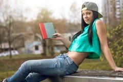 Mädchen in den Jeans ein Buch auf Bank lesend Stockbild