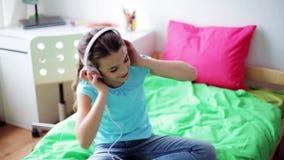 Mädchen in den Kopfhörern zu Hause hörend Musik stock footage