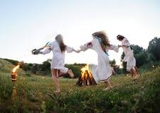 Mädchen in den ukrainischen nationalen Hemden, die um ein Lagerfeuer tanzen Midsumer Lizenzfreie Stockfotos