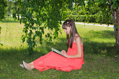Mädchen in der Natur in einem roten Kleid liest ein Buch Lizenzfreie Stockfotografie