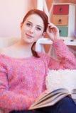 Mädchen in der rosa Strickjacke mit Buch Stockbild