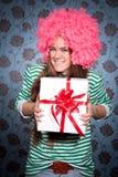 Mädchen in der rosafarbenen Perücke mit Geschenk Stockfotografie