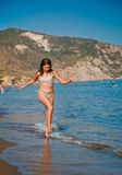 Mädchen des jungen jugendlich, das mit Wellen am Strand spielt. Lizenzfreie Stockfotos