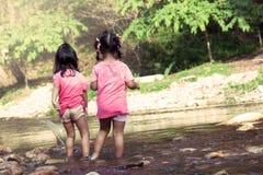 Mädchen des Kind zwei, die den Spaß, zum im Wasserfall zusammen zu spielen haben Stockbild