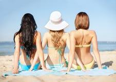 Mädchen, die auf dem Strand ein Sonnenbad nehmen Lizenzfreies Stockbild