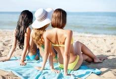 Mädchen, die auf dem Strand ein Sonnenbad nehmen Stockfotografie