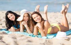 Mädchen, die auf dem Strand ein Sonnenbad nehmen Lizenzfreie Stockbilder