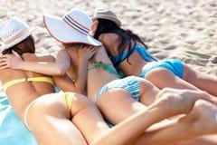 Mädchen, die auf dem Strand ein Sonnenbad nehmen Stockbild