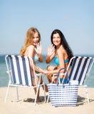 Mädchen, die auf den Strandstühlen ein Sonnenbad nehmen Stockbilder