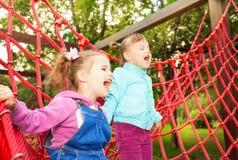 Mädchen, die auf Netz des Spielplatzes schreien und stehen Lizenzfreie Stockfotos
