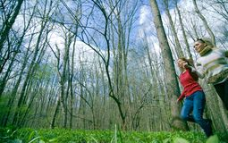 Mädchen, die durch einen Wald laufen Stockbilder