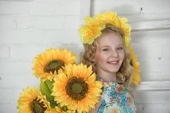 Mädchen in einem Baumwollkleid in einem Kranz von gelben Blumen Stockfotografie