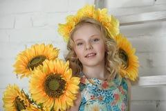 Mädchen in einem Baumwollkleid in einem Kranz von gelben Blumen Stockfoto