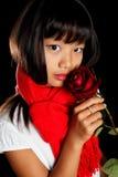 Mädchen in einem roten Schal mit einer Rose Stockfoto
