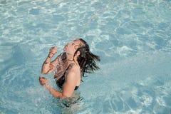 Mädchen in einem Swimmingpool, der nasses Haar wirft Stockfotos