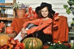 Mädchen in einer orange Strickjacke und in einem Hut in Halloween-Hexe Stockbild