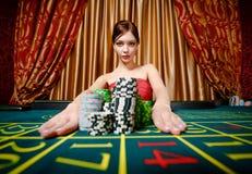 Mädchen gewinnt und nimmt Stapel der Chips weg Lizenzfreies Stockfoto