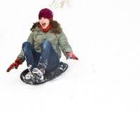Mädchen hat Spaß, indem sie hinunter den schneebedeckten Hügel sledging Stockfotografie