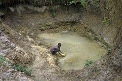 Mädchen holt unhygienisches Trinkwasser von einem Brunnen Stockbild