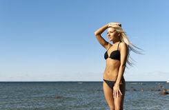 Mädchen im Bikini, der nahe dem Meer aufwirft Stockbilder
