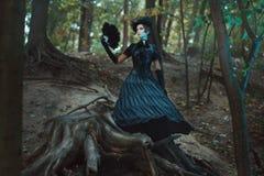 Mädchen im gotischen Kleid, das unter dem Baumstumpfwald steht Lizenzfreie Stockbilder