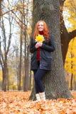Mädchen im Herbstwald halten Blätter in den Händen, Stand nahe großem Baum Lizenzfreies Stockfoto