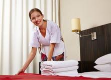 Mädchen im Hotelzimmer, das Bett macht Stockbild