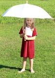 Mädchen im Rot mit weißem Regenschirm Stockbild