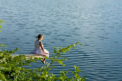Mädchen im Sommerkleid, das an der Plattform über Wasser sitzt Lizenzfreies Stockfoto